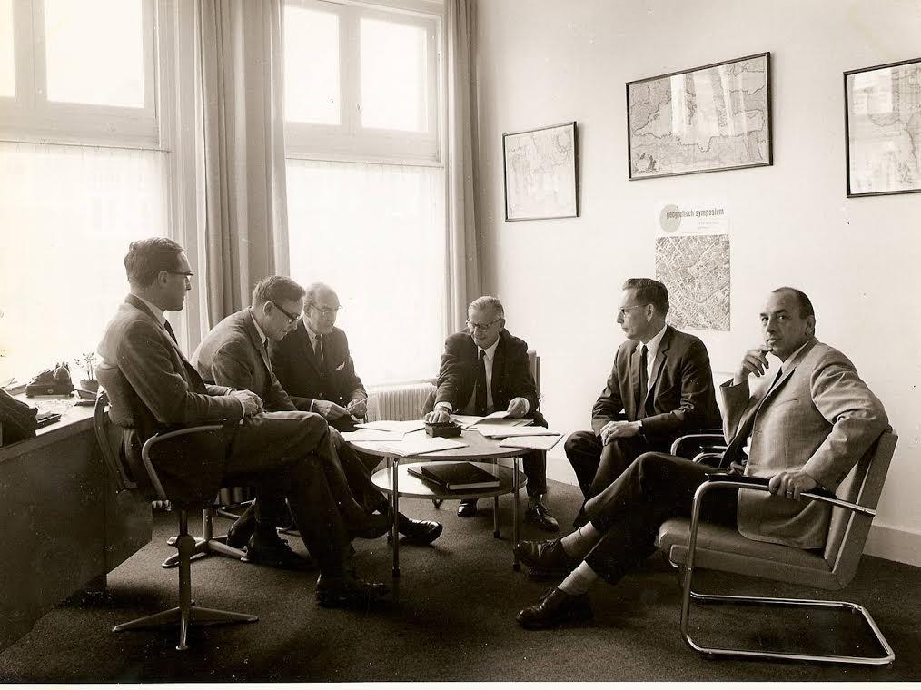 De wetenschappelijke staf bijeen op Keuning's werkkamer in het Geografisch Instituut aan de Kraneweg (1967). Van links naar rechts Chris van Welsenes, Jan de Vries, Wander de Jong, professor Keuning, de heer Dieperink (directeur van de Provinciaal Planologische Dienst Groningen, en part time docent planologie) en Gerrit Smit. De foto maakt deel uit van een fotoreportage die in 1967 werd gemaakt voor een stuk in de voorloper van de latere Universiteitskrant ('Der Clercke Cronike') over het pand Kraneweg 74 als nieuwe behuizing (sinds juni 1966) van de Subfaculteit der Geografie. De wetenschappelijke staf bijeen op Keuning's werkkamer in het Geografisch Instituut aan de Kraneweg (1967). Van links naar rechts Chris van Welsenes, Jan de Vries, Wander de Jong, professor Keuning, de heer Dieperink (directeur van de Provinciaal Planologische Dienst Groningen, en part time docent planologie) en Gerrit Smit. De foto maakt deel uit van een fotoreportage die in 1967 werd gemaakt voor een stuk in de voorloper van de latere Universiteitskrant ('Der Clercke Cronike') over het pand Kraneweg 74 als nieuwe behuizing (sinds juni 1966) van de Subfaculteit der Geografie.